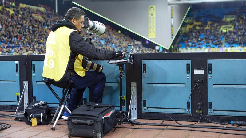 Een fotograaf die een Surface Pro gebruikt in een stadion.