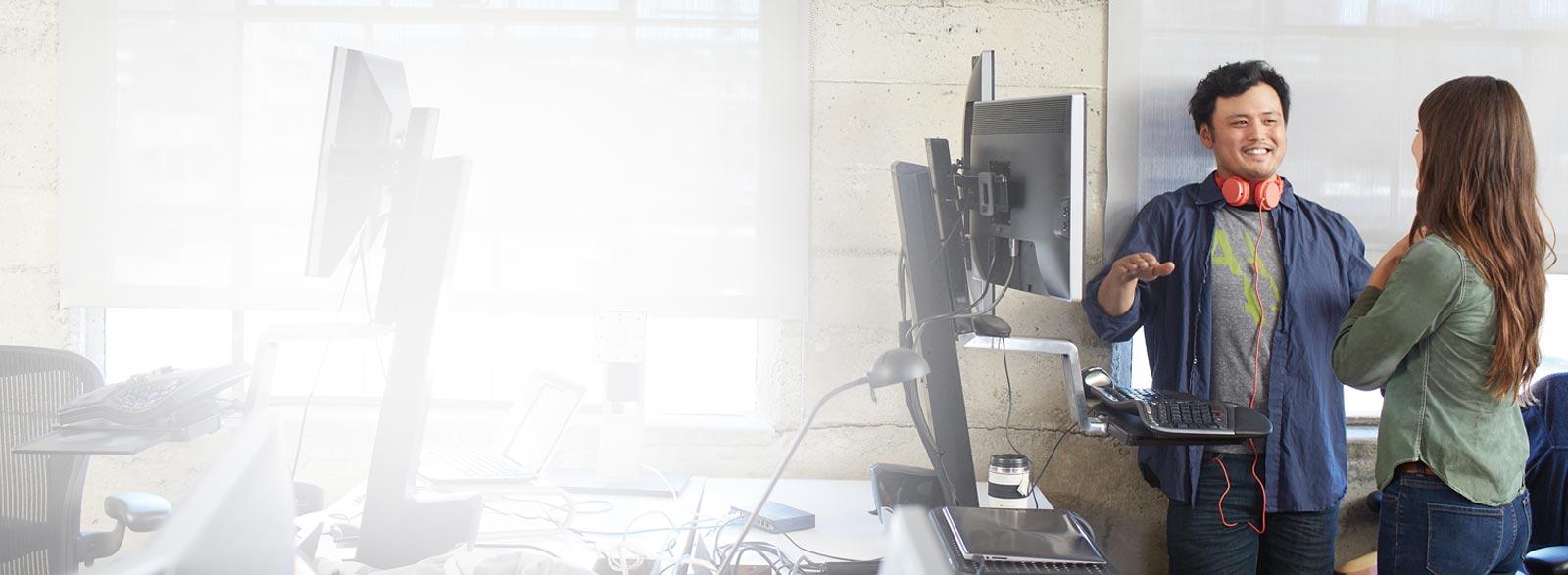 Een man en een vrouw staand in een kantoor, aan het werk met Office 365 Business Premium.