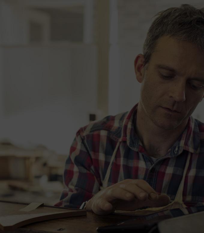 Een man in een workshop met Office 365 Business op een tablet.
