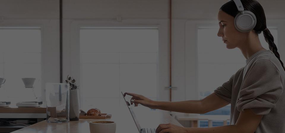 Foto van een persoon met een hoofdtelefoon aan een balie die een laptopscherm aanraakt