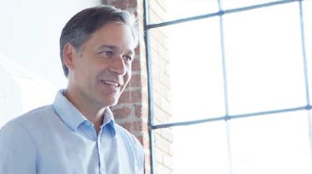 Een man die lachend voor een raam staat, lees artikel 'Werken als een netwerk: Waarom moderne bedrijven sociale media voor ondernemingen nodig hebben'