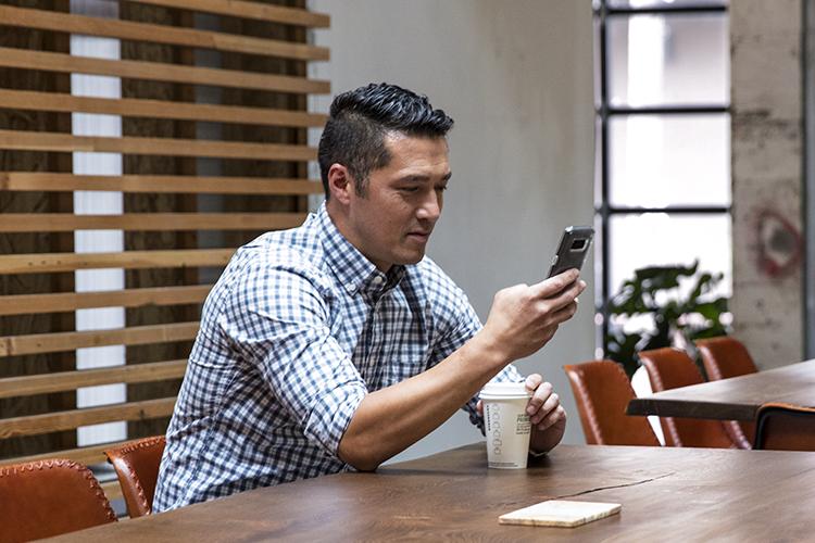Persoon die in een vergaderruimte zit en naar een mobiel apparaat kijkt