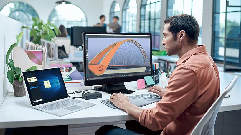 Man die aan zijn bureau op Surface Book werkt die is verbonden met een toetsenbord, muis en monitor via Surface-basisstation