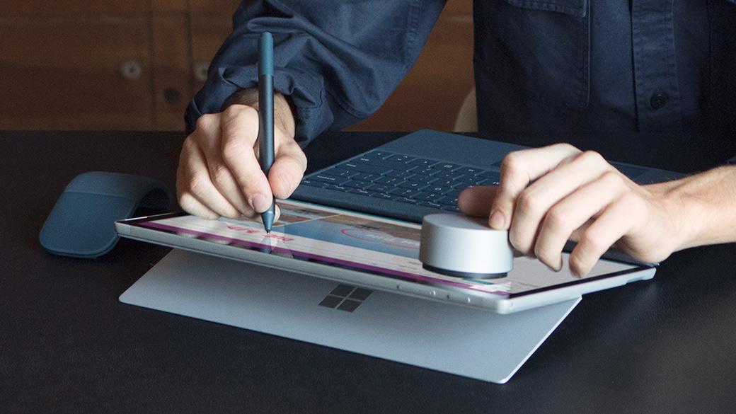 Iemand die een Surface-pen en Surface Dial gebruikt met een Surface-apparaat.