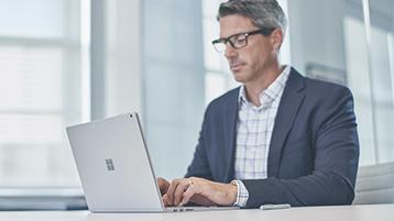 Een goed geklede zakenman die op zijn Surface-apparaat typt.