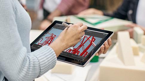 Vrouw die op Surface in tabletmodus aan het tekenen is met de Surface-pen.