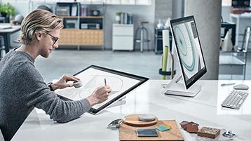 Man die met dial op het Surface Studio-scherm tekent in een moderne kantooromgeving met een andere Surface Studio tegenover hem