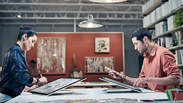 Man en vrouw die tegenover elkaar werken, beiden met Surface Studio in studiomodus