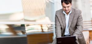 Een staande man die op zijn laptop werkt, informatie over functies en prijzen van Exchange Online
