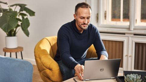 Man zit op een stoel en gebruikt een laptop