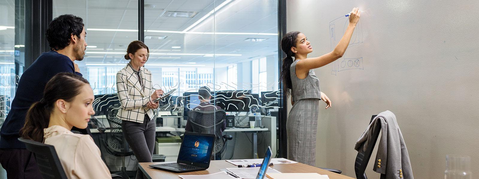 Vrouw die op whiteboard schrijft terwijl anderen apparaten bekijken