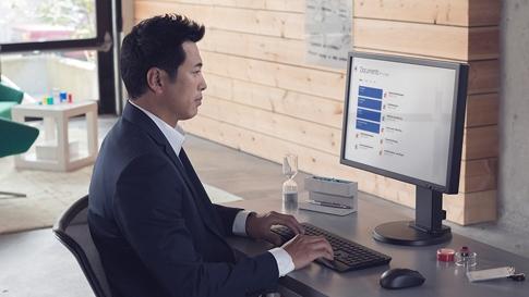 Man aan het werk op desktop