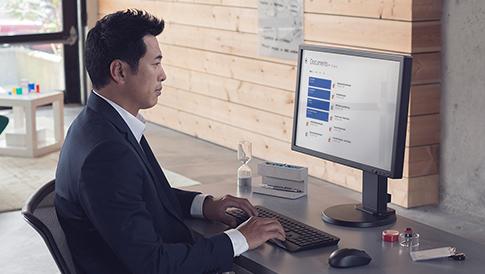 Zakenman typend op een desktopcomputer