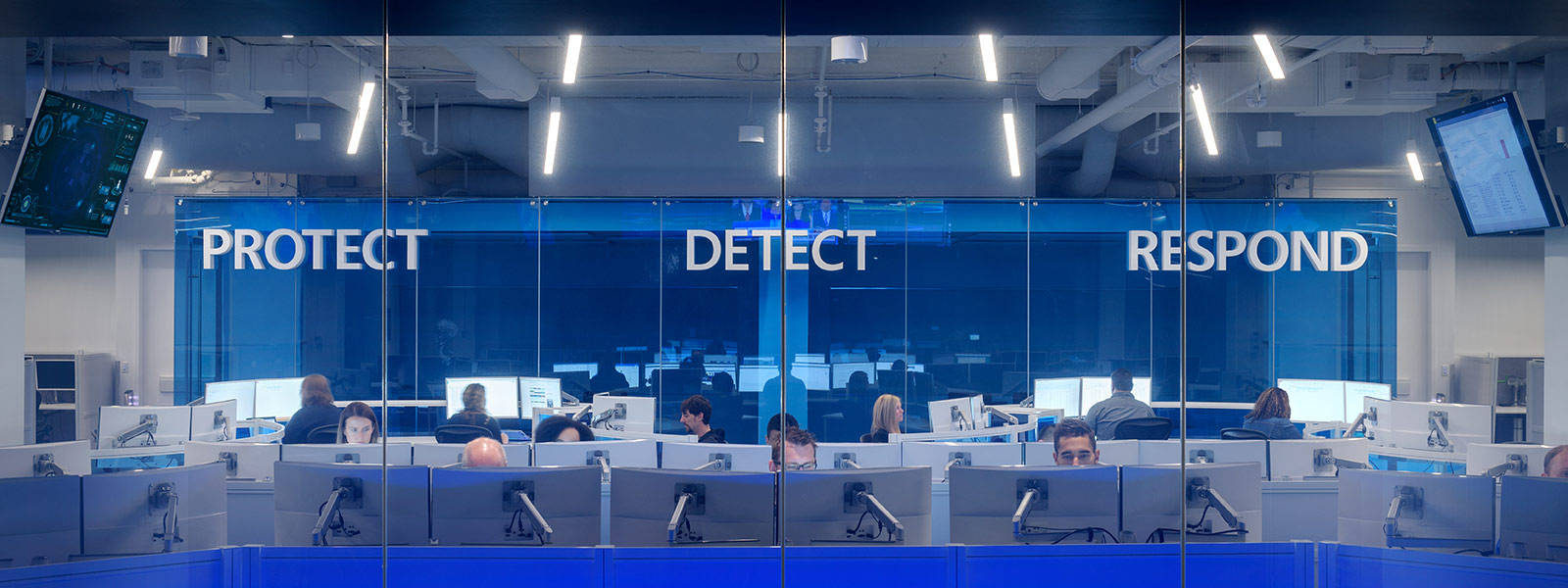 Mensen in een computerlokaal die werken aan Windows Defender ATP
