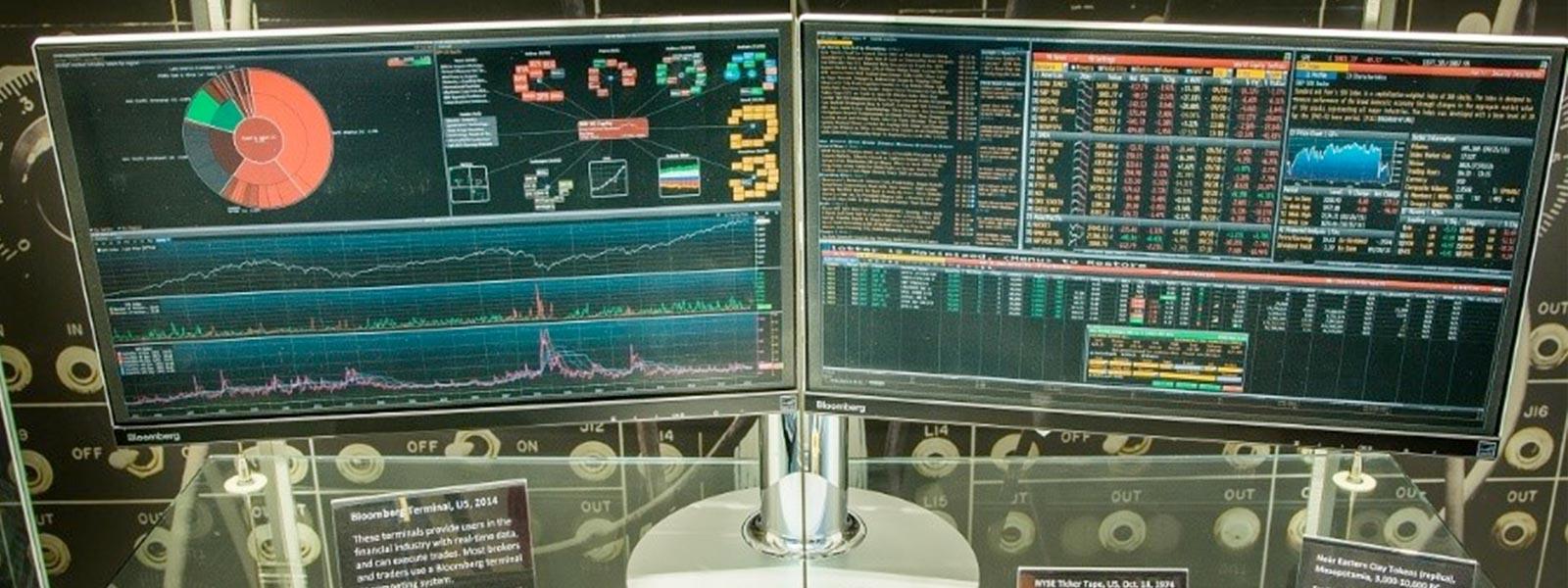 Twee monitoren met financiële grafieken