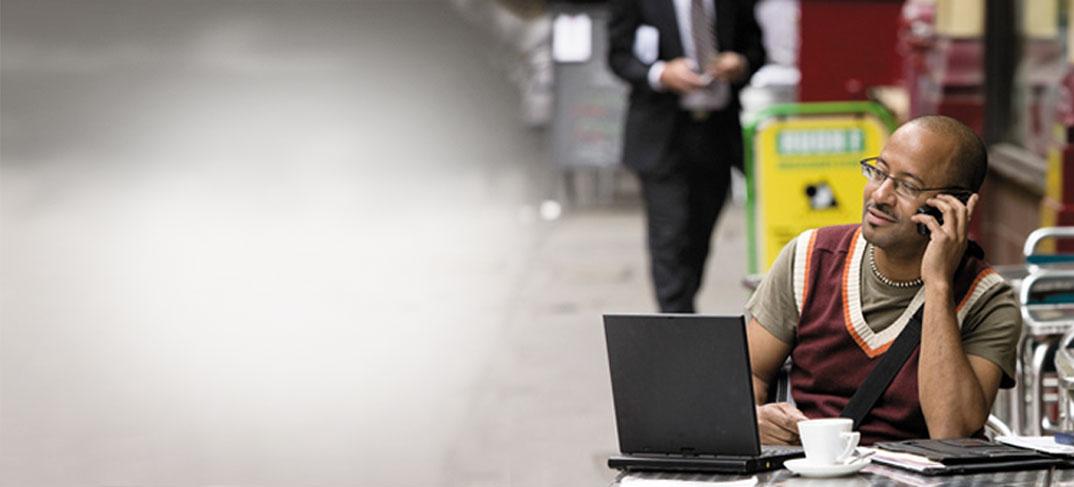 Een man met een telefoon en een laptop in een café, die zakelijke e-mail gebruikt via Exchange Server 2013.