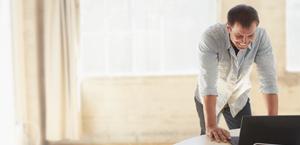 Een lachende man die over een geopende laptop leunt en Office 365 Business Essentials gebruikt.