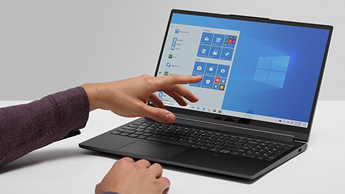 Ręka wskazująca na ekran startowy Windows 10 wyświetlany na ekranie laptopa
