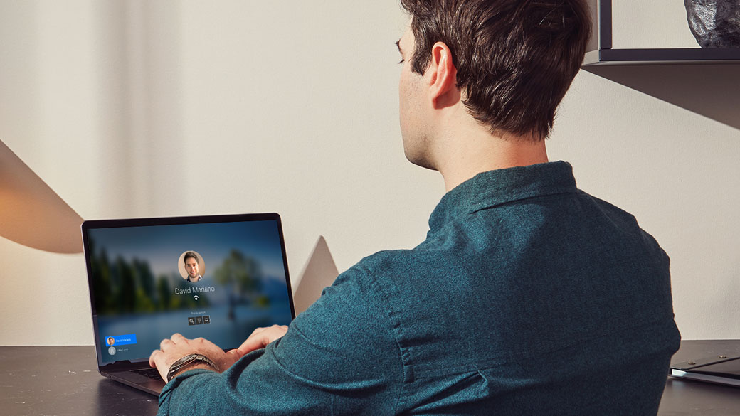 Siedząca przy biurku osoba loguje się do swojego laptopa wykorzystując do tego funkcję Windows Hello