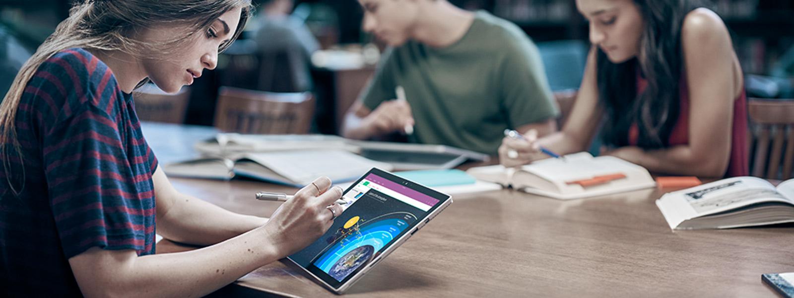 Student pracujący na urządzeniu Surface Pro 4 w bibliotece