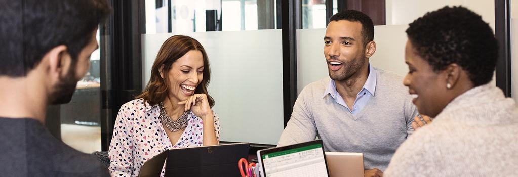 Grupa osób siedzi wokół stołu z laptopami, śmiejąc się i rozmawiając