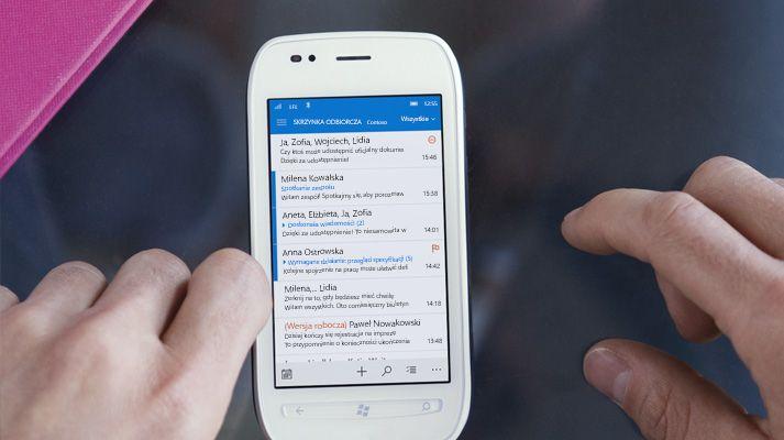 Dłoń naciskająca wiadomość na liście wiadomości e-mail w usłudze Office 365 na smartfonie.