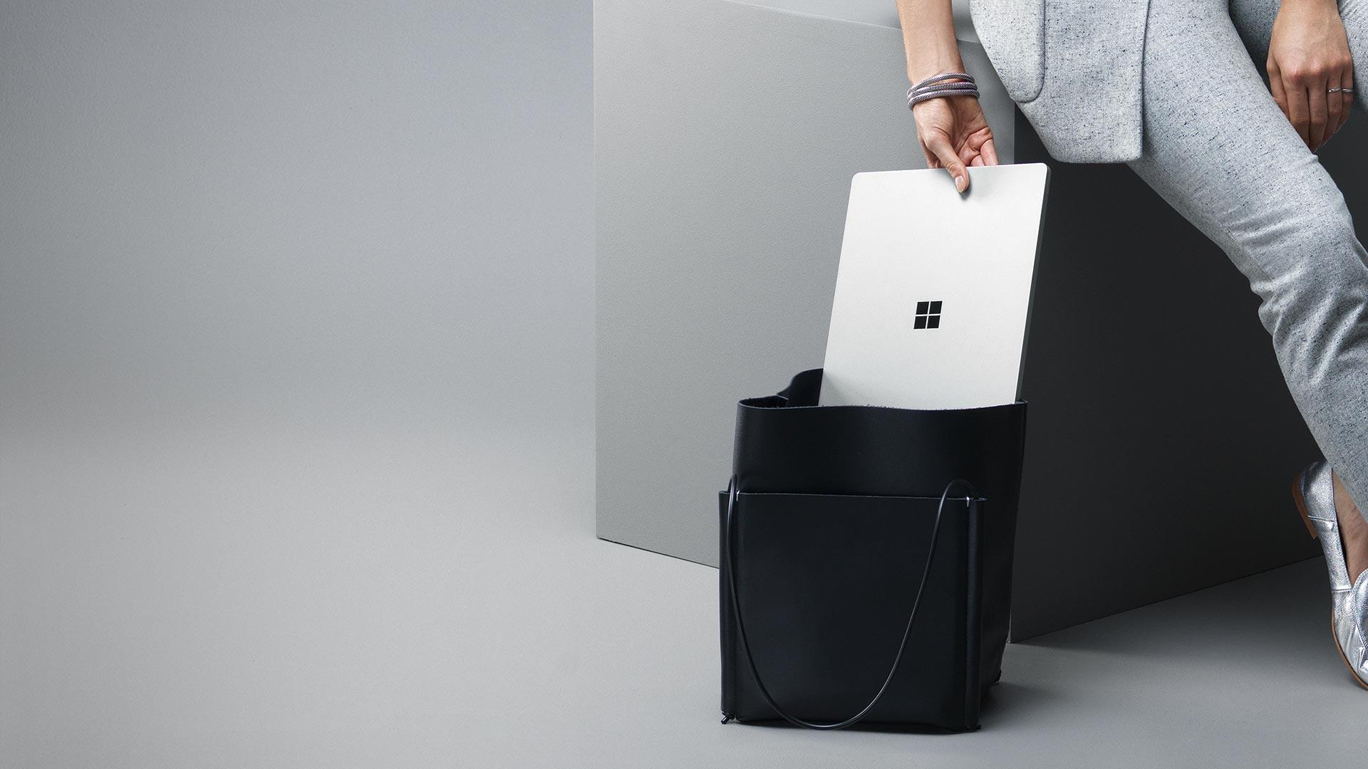 Modnie ubrana kobieta wkładająca tablet Surface Laptop wkolorze platynowym do torebki.