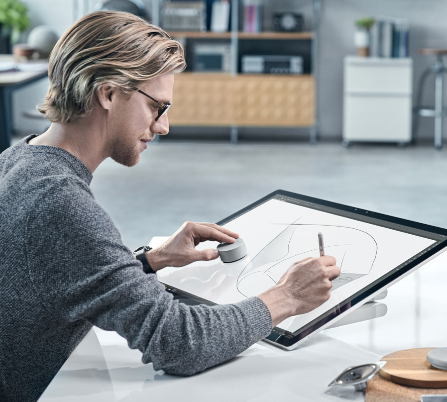 Mężczyzna korzystający z pióra Surface i akcesorium Surface Dial na urządzeniu Surface Studio