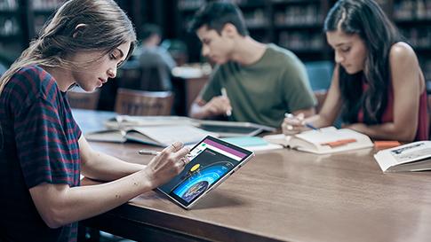 Kobieta rysująca na urządzeniu Surface w trybie tabletu przy użyciu pióra Surface.