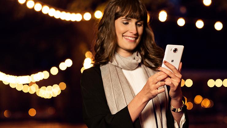 Kobieta patrząca na smartfon zsystemem Windows10