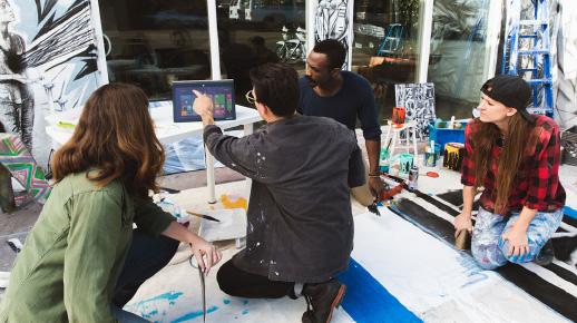 Grupa artystów patrzących na laptopa