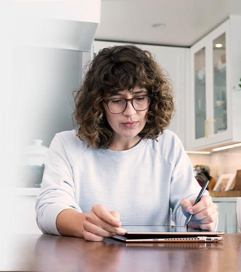 Mulher desenha com uma caneta digital em um computador tablet