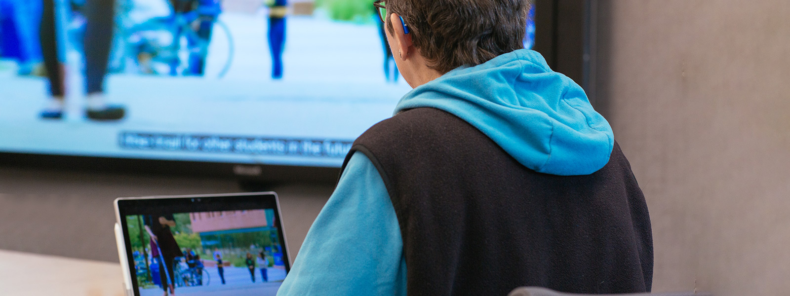 Uma mulher que usa um aparelho auditivo assiste a uma apresentação em vídeo com legendas