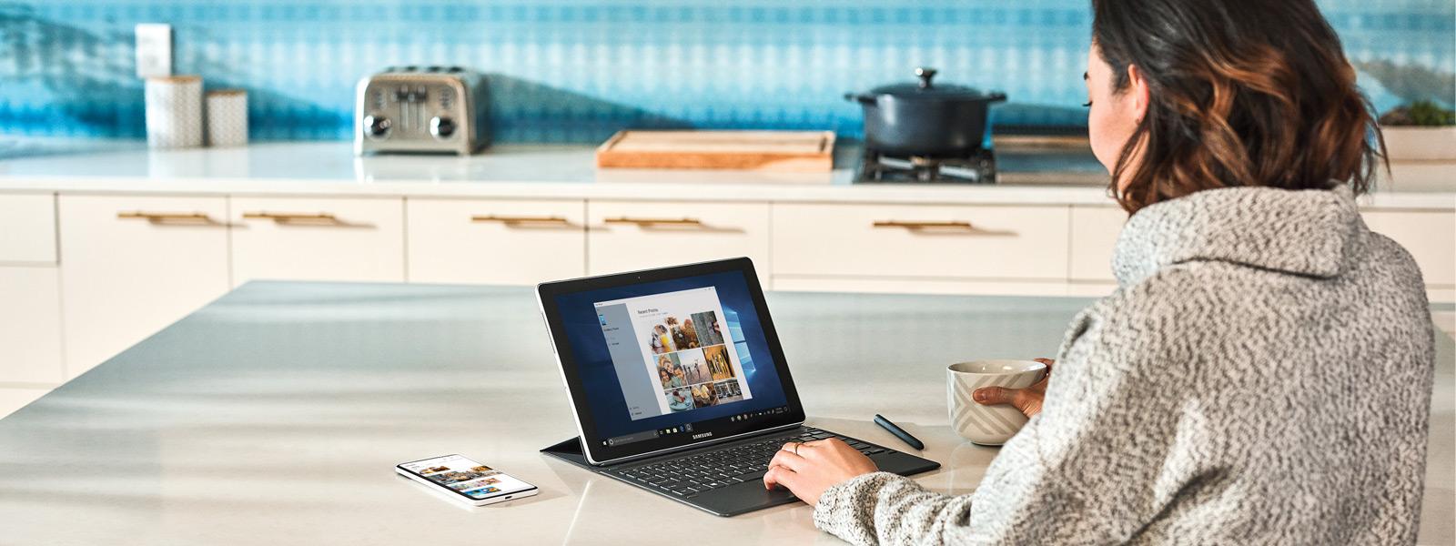 Mulher sentada ao balcão da cozinha usando um laptop com Windows 10 por meio do celular