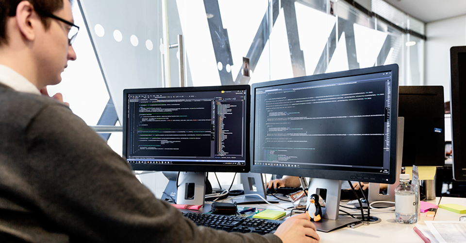 Fotografia de uma pessoa em um escritório compartilhado, trabalhando em uma mesa com dois monitores grandes exibindo informações