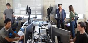 Cinco pessoas em um ambiente de trabalho compartilhado, usando PCs ou em reunião.