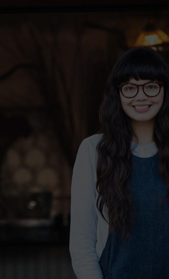 Uma mulher jovem de óculos, sorrindo, do lado de fora, ao lado de vasos com flores cortadas.