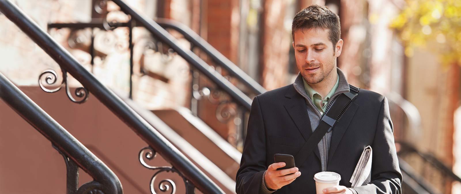 Um homem segurando um smartphone, usando o Office 365 Enterprise E1.