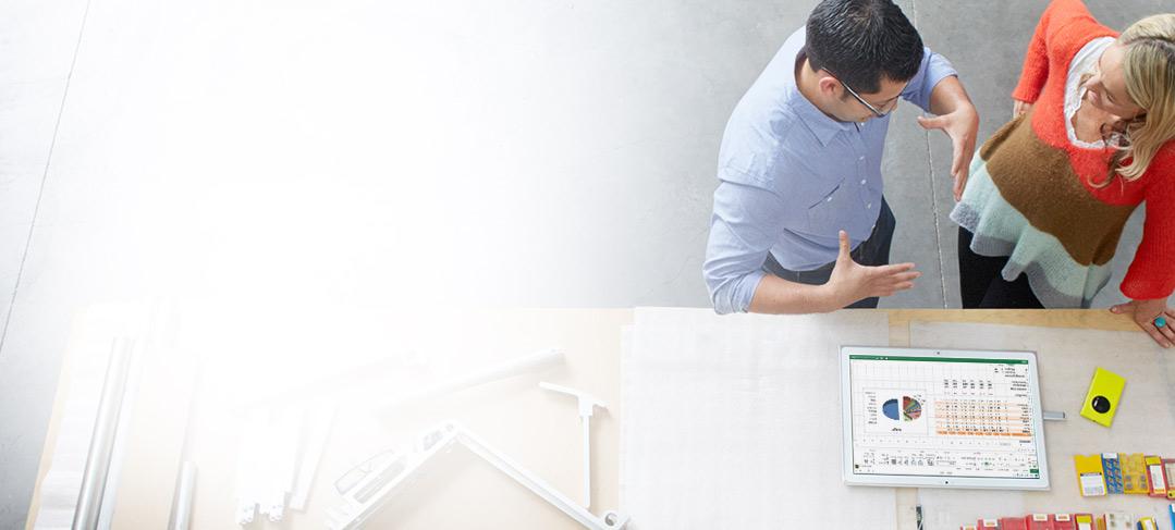 Um homem e uma mulher ao lado de uma mesa de desenho usando o Office 365 ProPlus em um tablet.