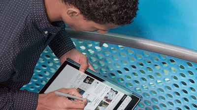 um homem olhando para a tela de um tablet executando o SharePoint