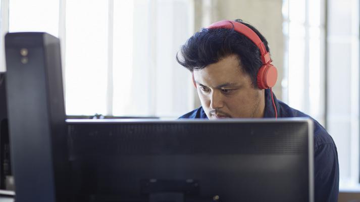 Um homem com fones de ouvido trabalhando em um computador desktop, usando o Office 365 para simplificar a TI.