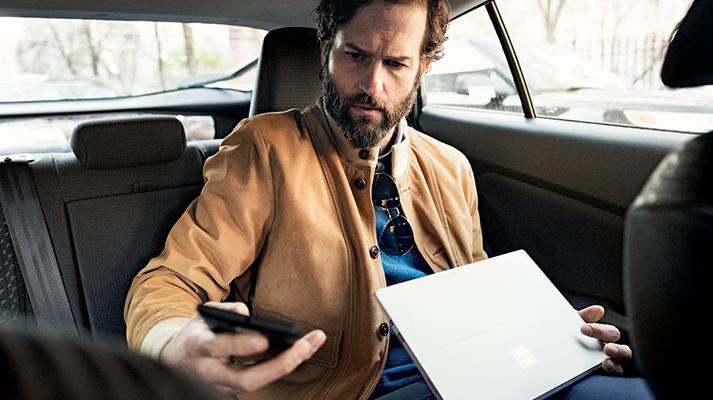 Um homem sentado em um carro com um laptop no colo e olhando para um telefone