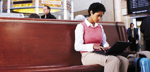 Uma mulher em uma estação de trem trabalhando em um laptop; saiba mais sobre os recursos e preços da Proteção do Exchange Online