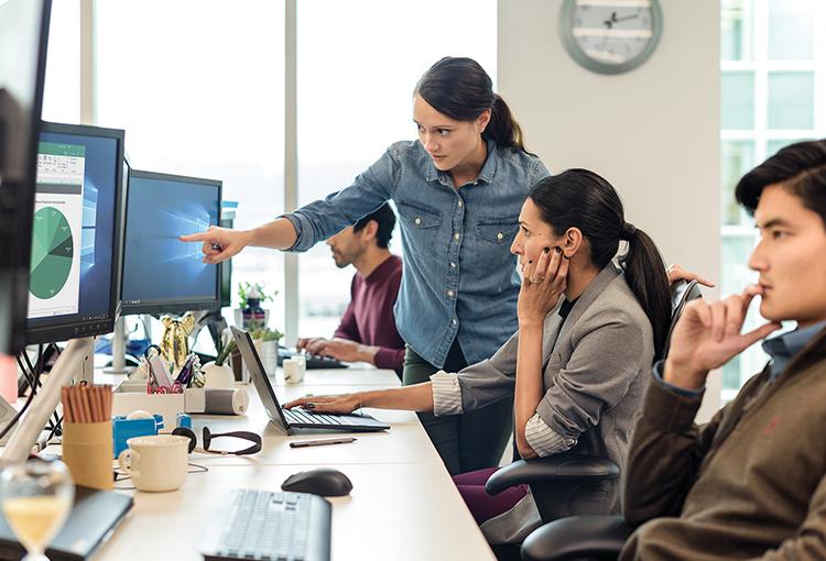 Pessoas em um escritório analisando um gráfico de pizza no monitor.