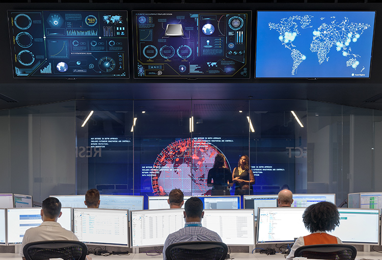 Pessoas em um datacenter monitorando o fluxo de dados em frente a monitores grandes pendurados