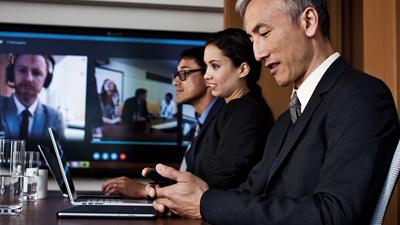 Três pessoas em uma videoconferência em uma sala de conferência