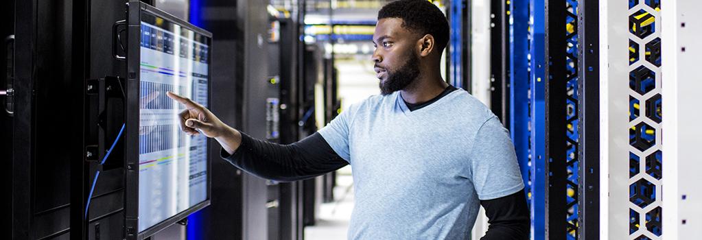Homem usando uma tela fixada em uma parede na sala de servidores