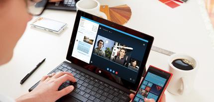 Uma mulher usando o Office 365 em um tablet e um smartphone para colaborar em documentos.