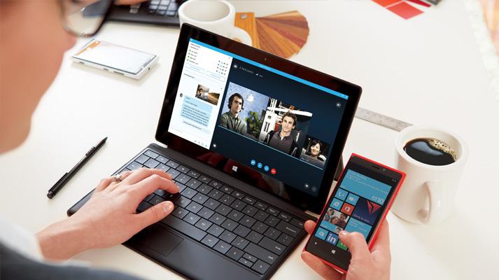 Mulher usando o Office 365 no tablet e no smartphone para colaborar em documentos.