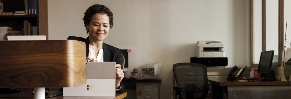 Mulher sorrindo enquanto trabalha em um escritório no Surface